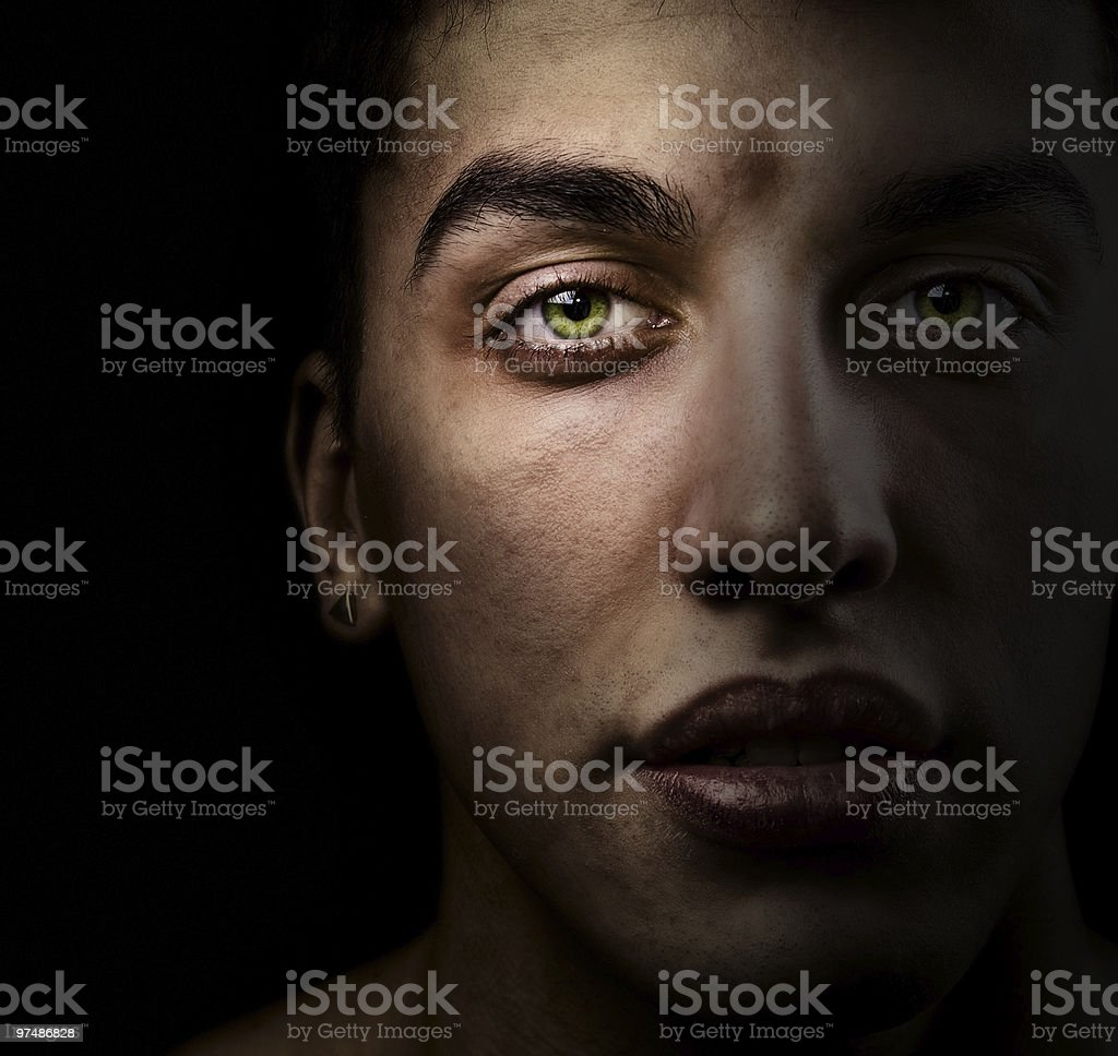 Face of beautiful man with green eyes in the shadow stock photo