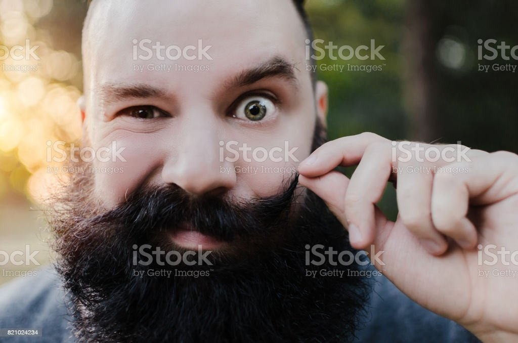 face of cute man with long beard and green eye stock photo