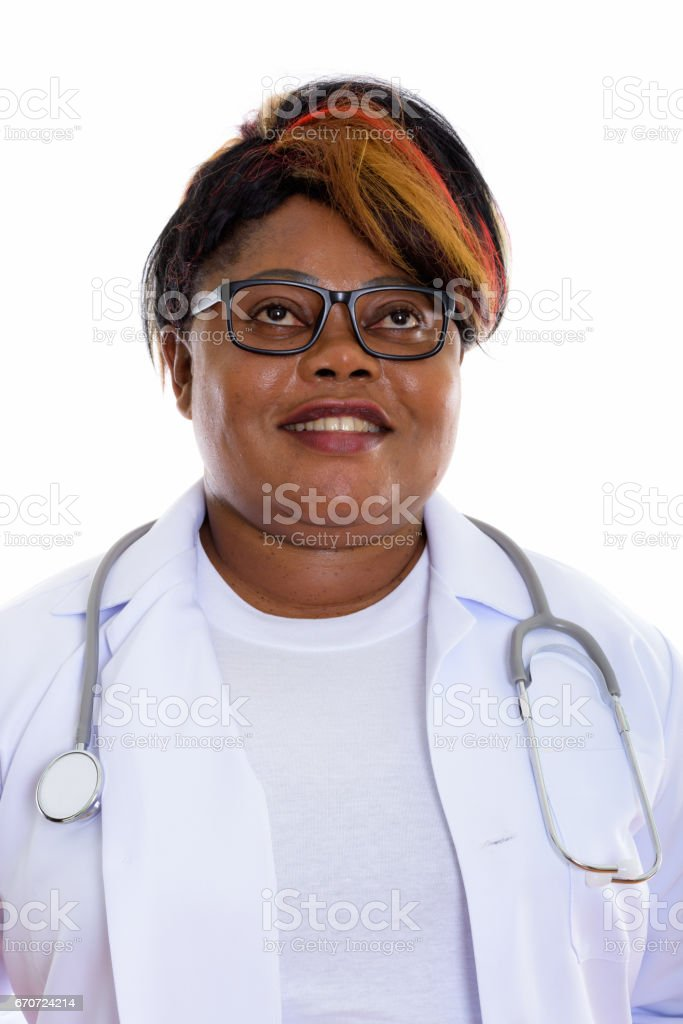 Face of happy fat black African woman doctor smiling and thinking while wearing eyeglasses stock photo