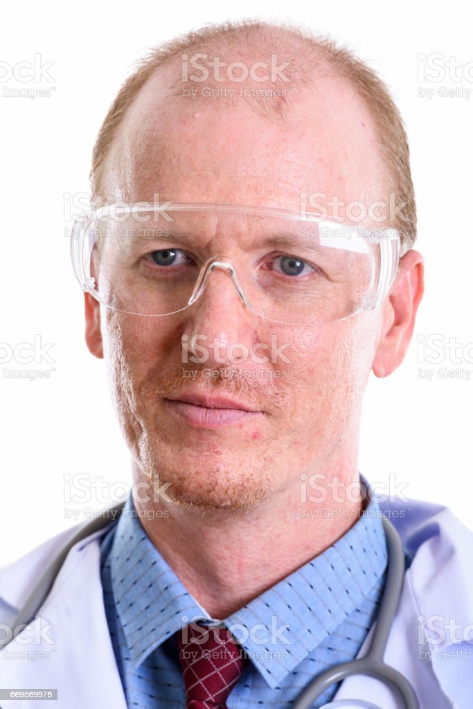 Face of man doctor thinking while wearing protective glasses stock photo
