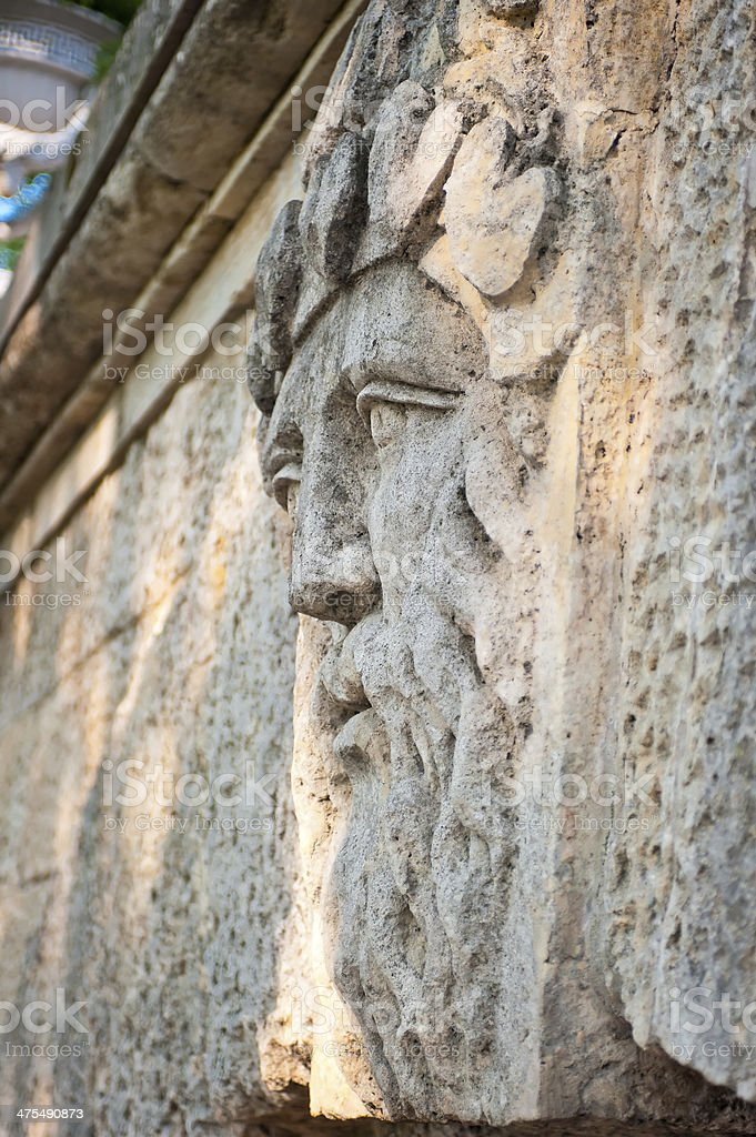 face of  man with a beard carved in stone stock photo