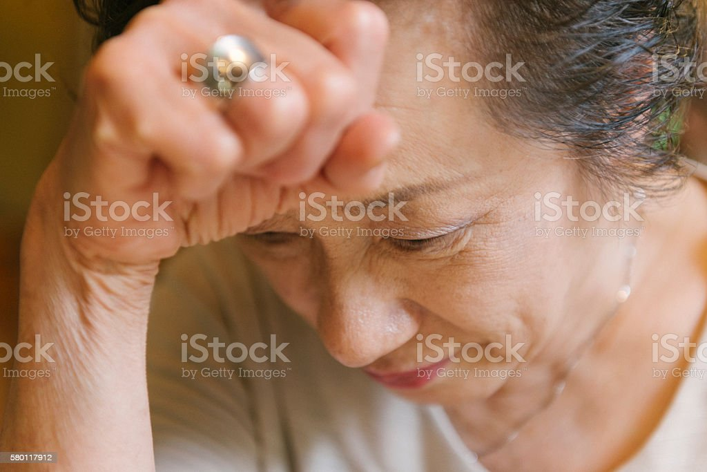 Face of Mature Japanese Woman Feeling Migraine Headache Pain stock photo