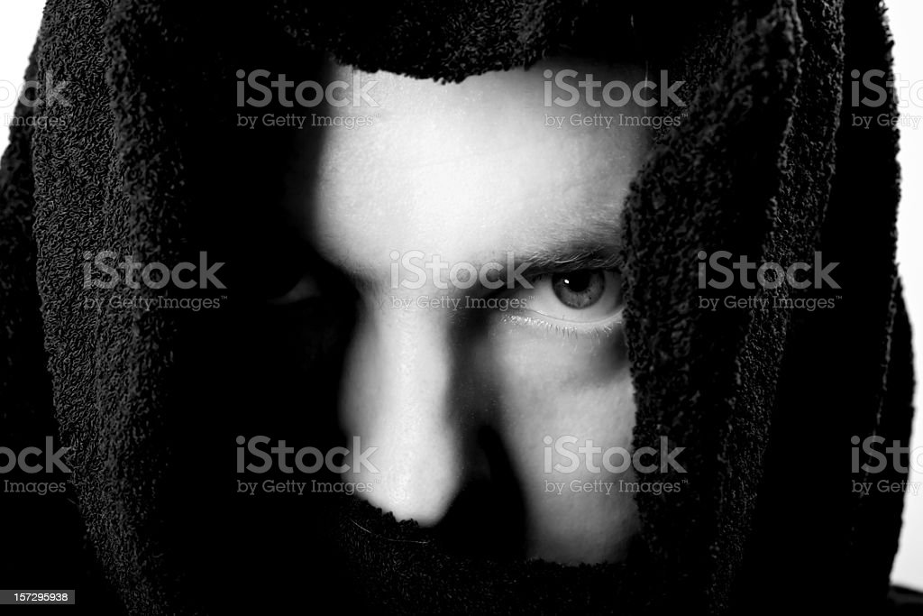 Face of scary young man in dark habit watching B&W royalty-free stock photo