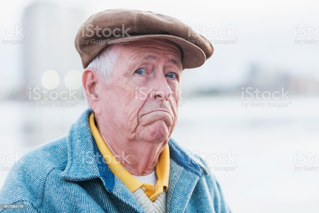 Face of senior man wearing flat cap, frowning stock photo