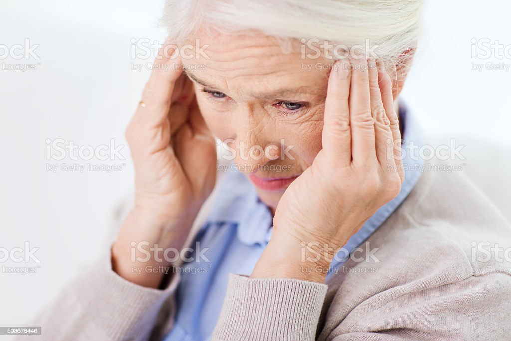 face of senior woman suffering from headache stock photo