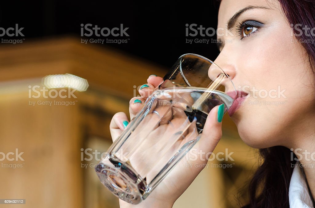 Face of the girl or woman close up drinking water stock photo