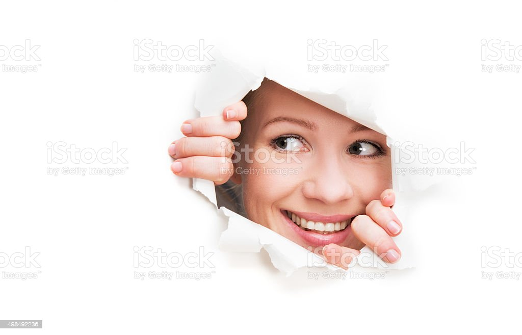 face of  woman peeking through hole torn in white poster stock photo