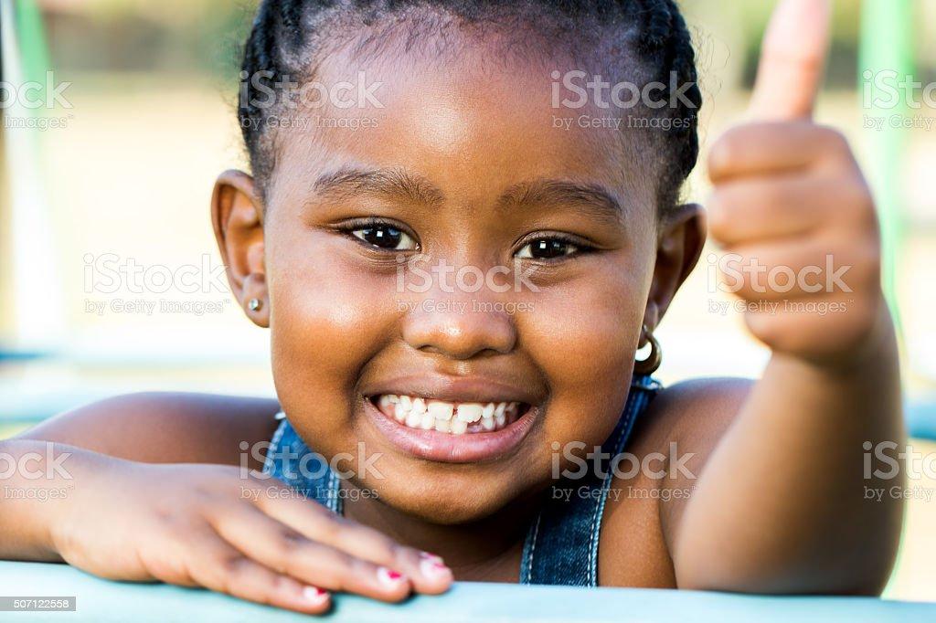 Photo de visage de jeune fille africaine faisant thumbs vers le haut en plein air. photo libre de droits