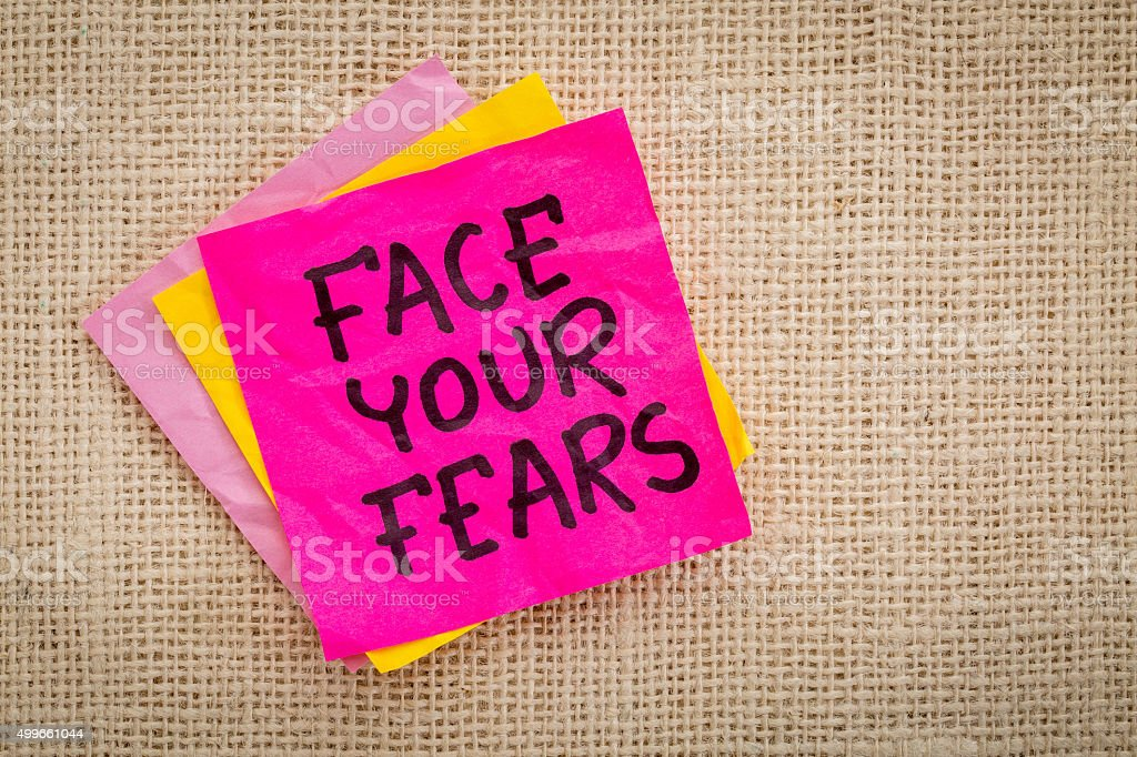 Face your fears advice on sticky note stock photo