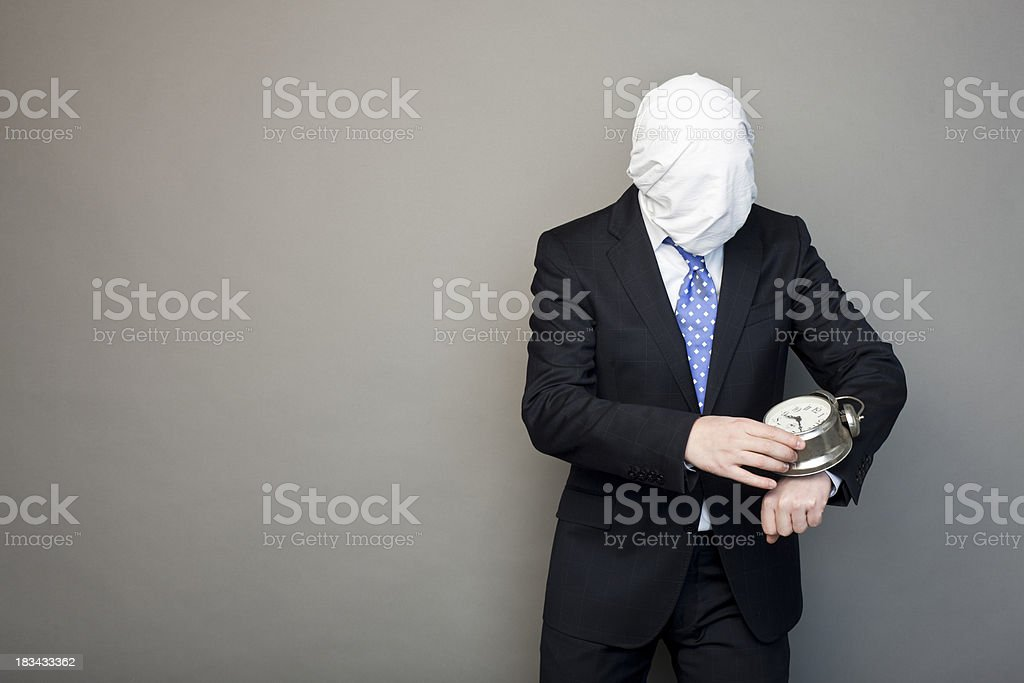 faceless man playing with a table clock stock photo