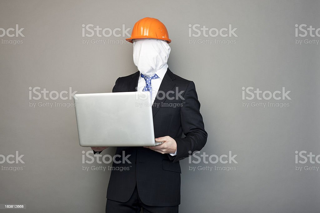 faceless man wearing construction cap keeping a laptop in hands royalty-free stock photo