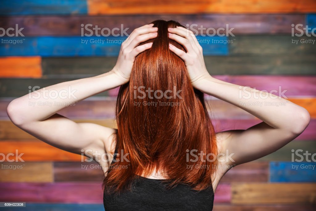 Faceless woman holding her head. Red hair covered face stock photo