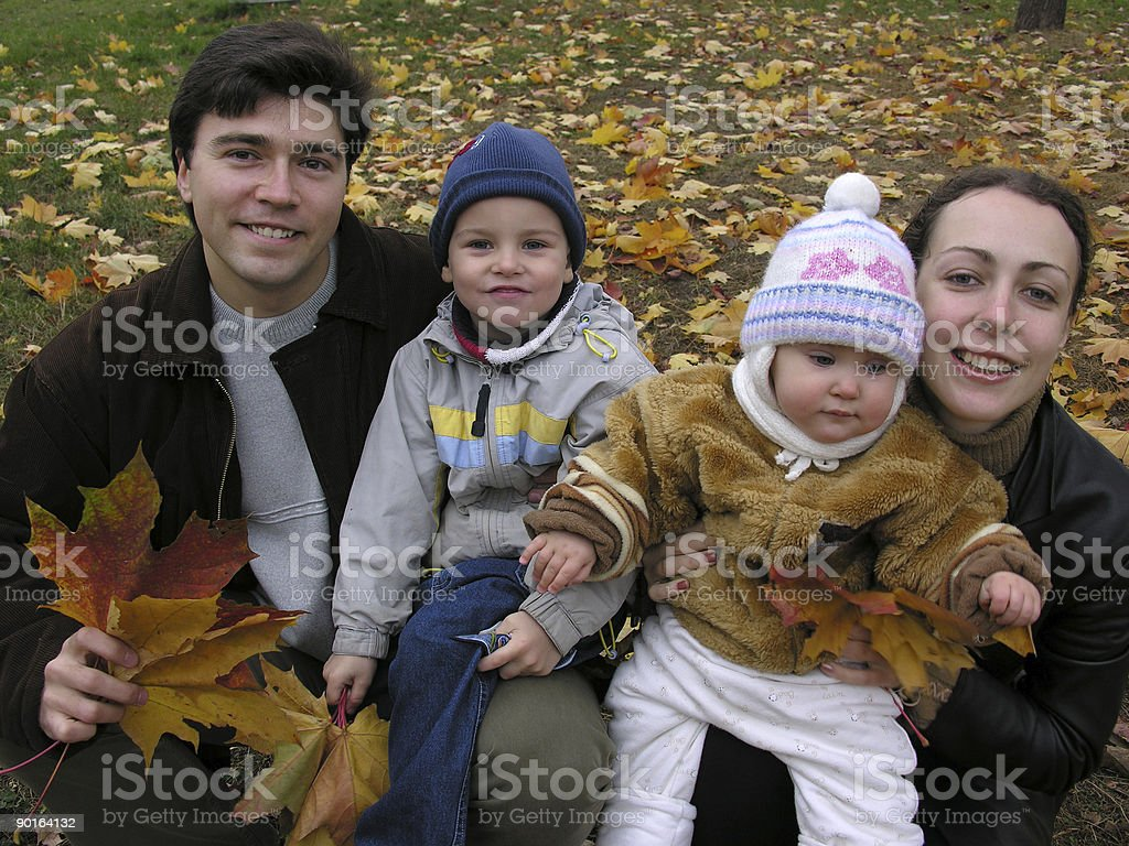 faces family of four on maple leaves royalty-free stock photo