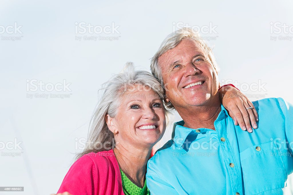 Faces of a mature, affectionate couple outdoors stock photo