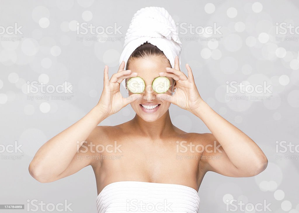 Facial skin care with cucumber against silver sparkling background stock photo