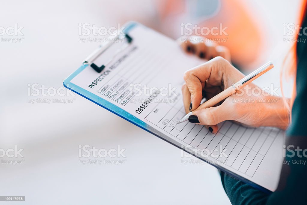 Facility management technician filling inspection form stock photo