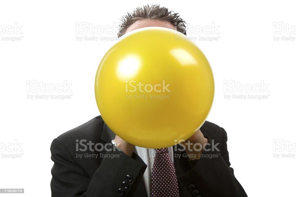 Facing Businessman Blowing Up  a Balloon stock photo