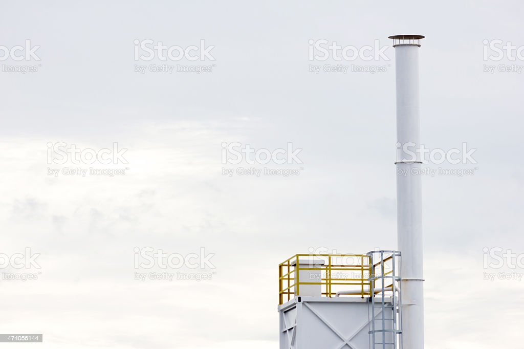 Factory chimney in the white sky stock photo