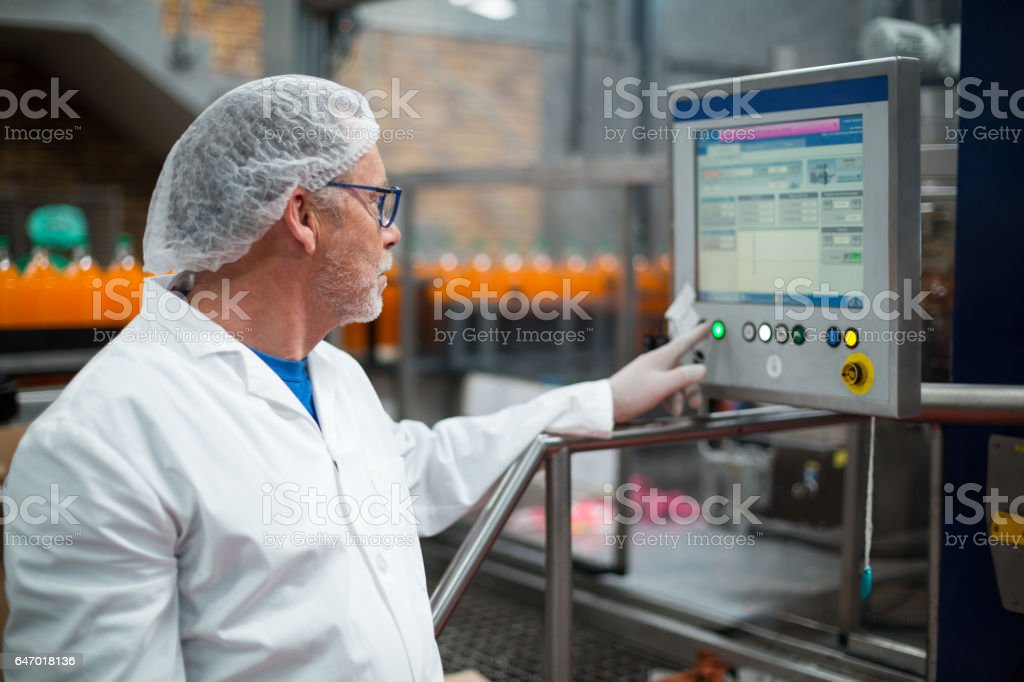 Factory engineer operating machine in factory stock photo
