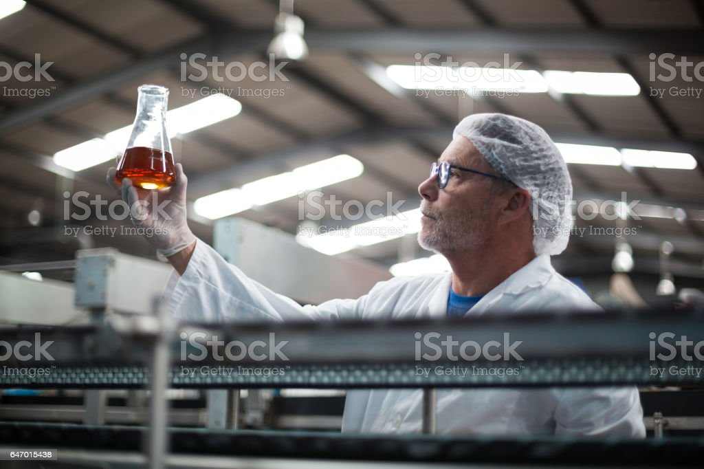 Factory engineers checking a sample of drink stock photo