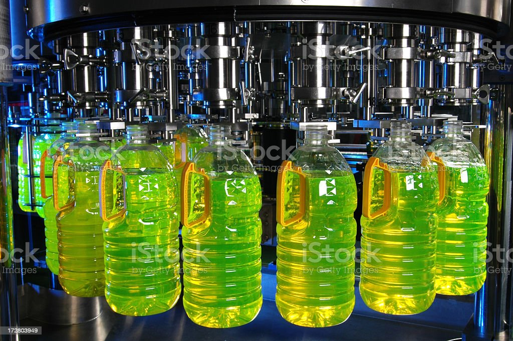 Factory filling bottles with a liquid stock photo