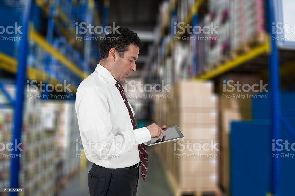 Factory manager checking inventory in stock room on touchscreen tablet stock photo