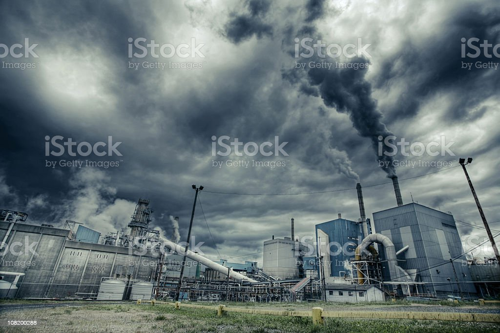 Factory smoke polluting air in a cloudy day stock photo
