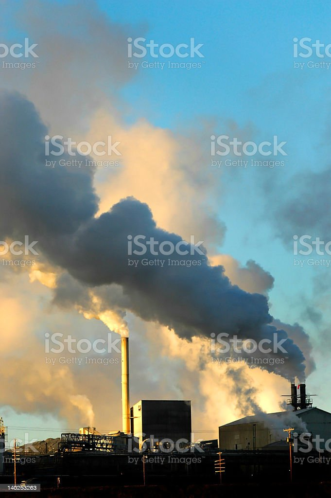 factory spewing smoke and pollution into the air stock photo