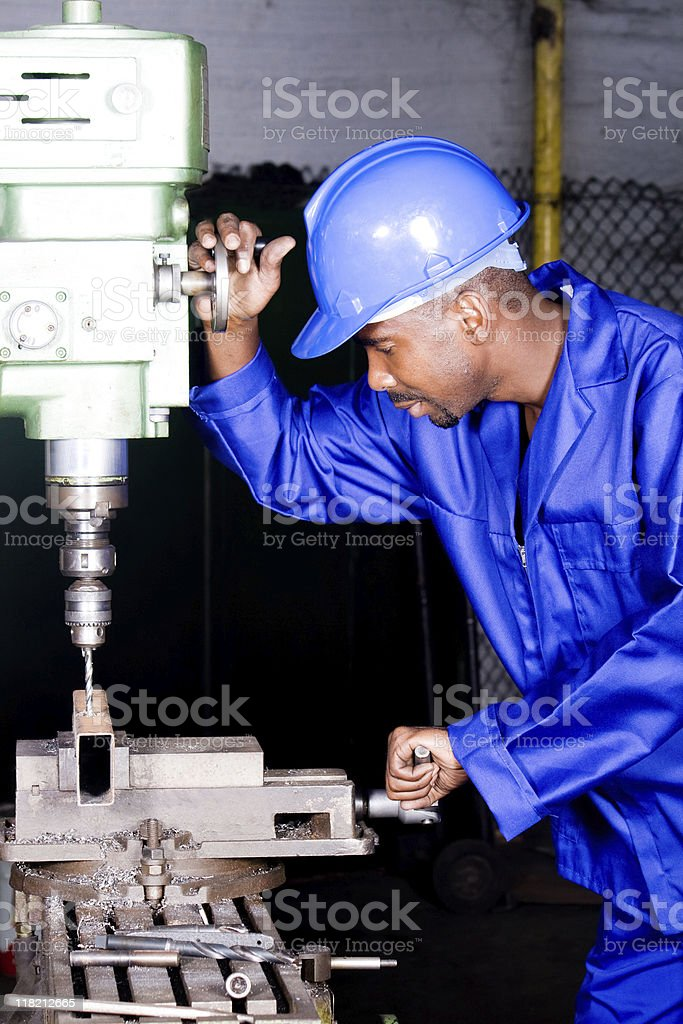 Factory worker attired in blue, using industrial drill royalty-free stock photo