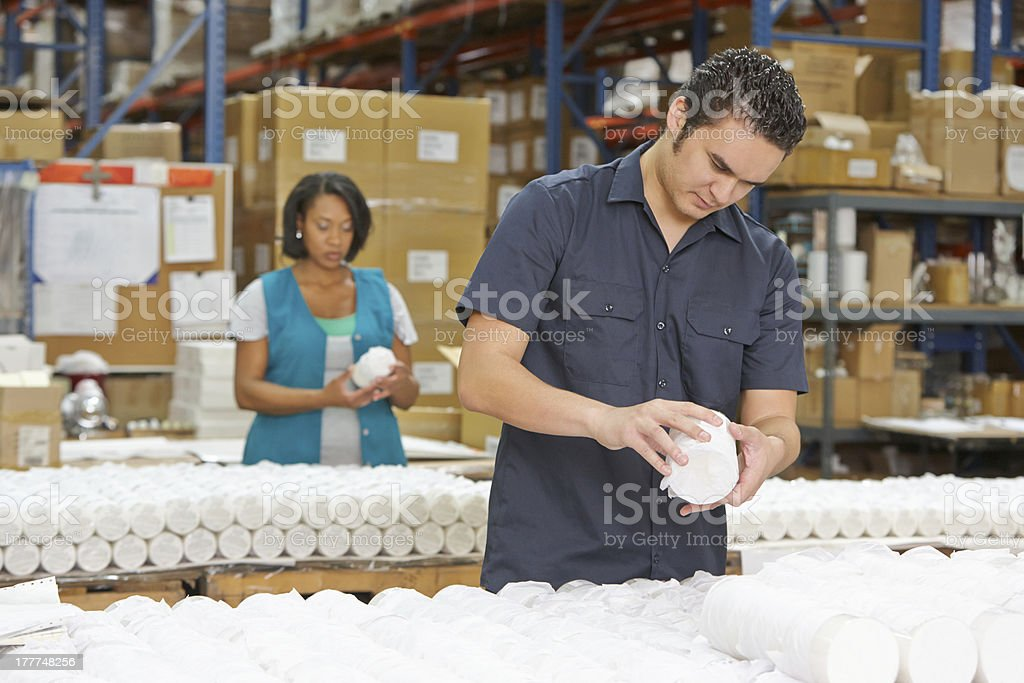 Factory Worker Checking Goods On Production Line stock photo