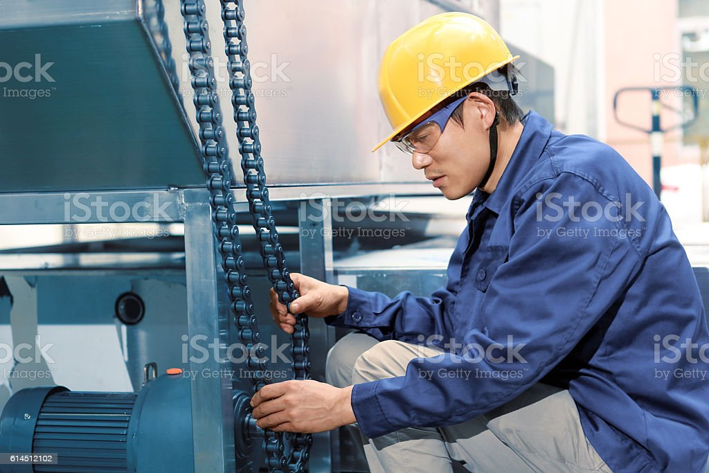 Factory worker holding chains stock photo