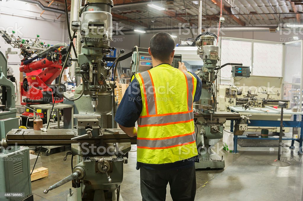 Factory Worker Mechanic Using Precision Machining Tool at Manufacturing Plant stock photo