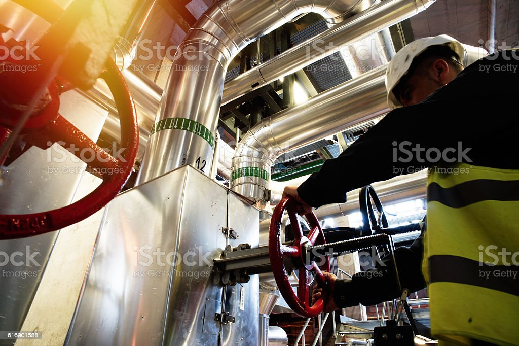 factory worker turning valve stock photo