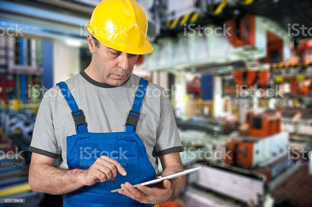 Factory worker using digital tablet to operate machinery stock photo