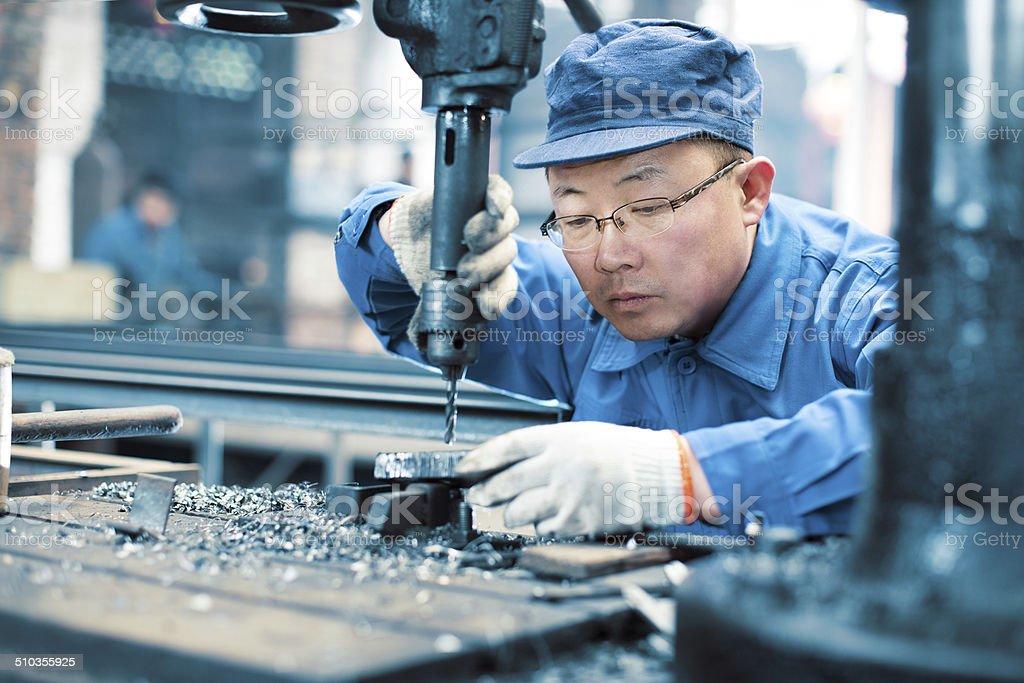 Factory worker using drilling machine stock photo