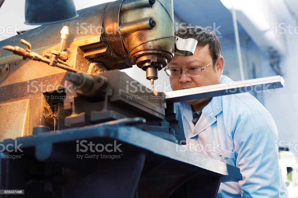 Factory worker using drilling machine stock photo