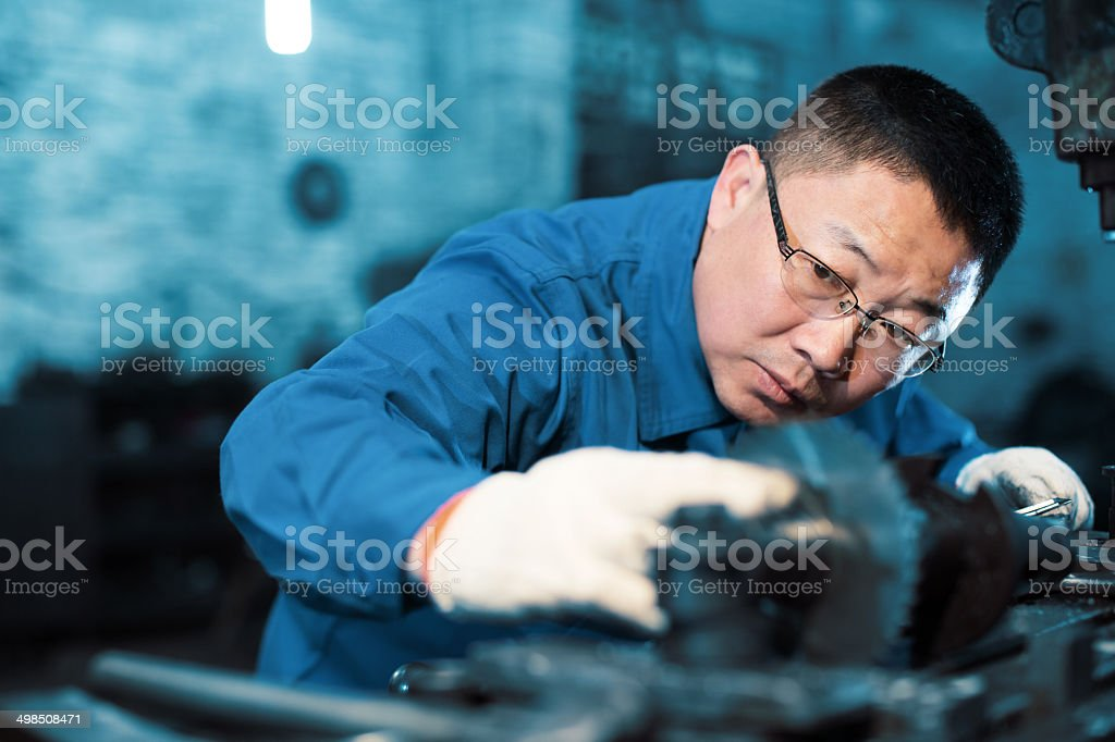 factory worker using electric saw stock photo