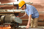 factory worker using electric saw