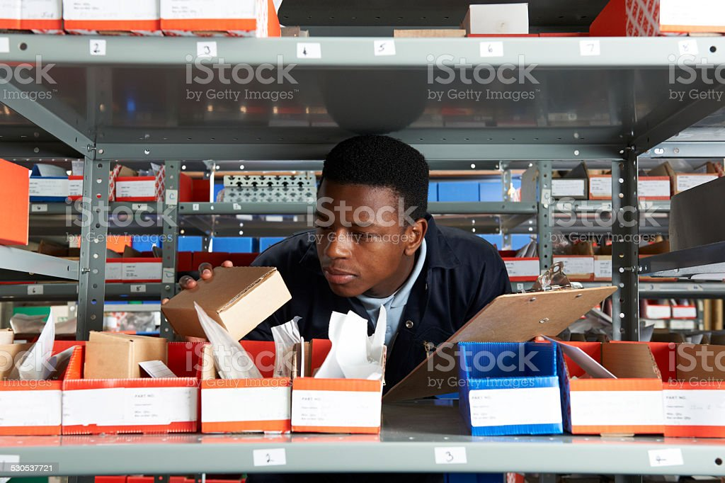 Factory Worker With Clipboard In Storeroom stock photo