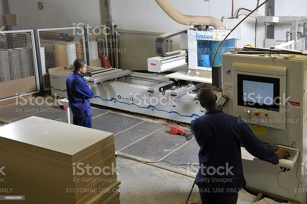 Factory workers operate router royalty-free stock photo