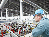 Factory-worker in hard-hat looking at factory floor