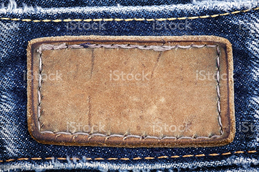 Faded blue jeans close-up on blank leather label stock photo
