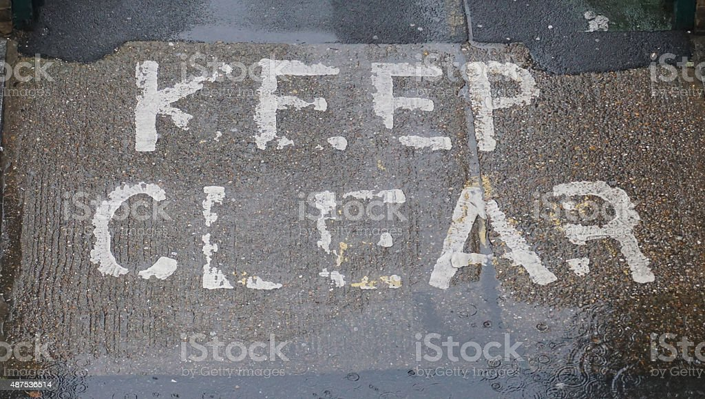 Fading keep clear sign on road stock photo