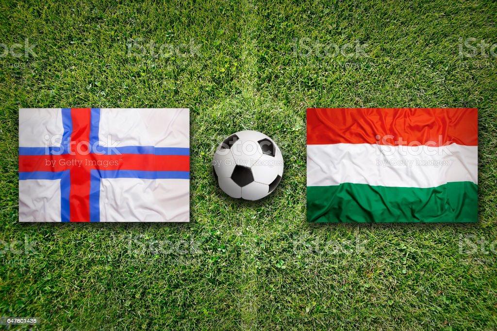 Faeroe Islands vs. Hungary flags on soccer field stock photo