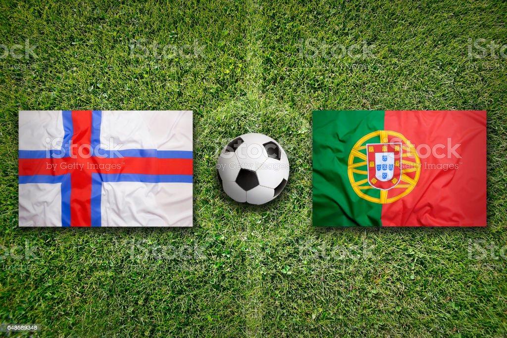 Faeroe Islands vs. Portugal flags on soccer field stock photo