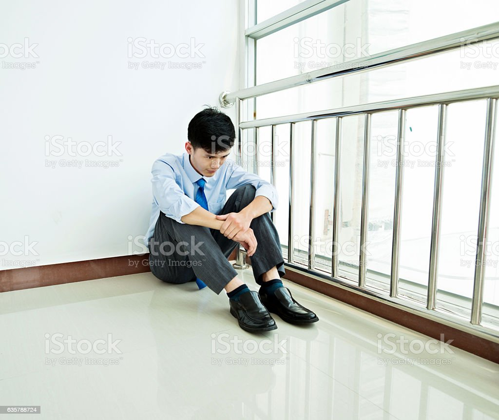 Failure of a businessman in corner stock photo