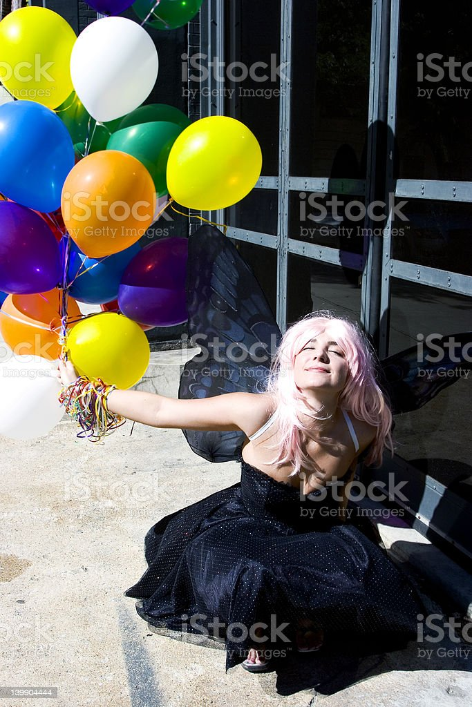 Fairy with balloons enjoying the sun royalty-free stock photo