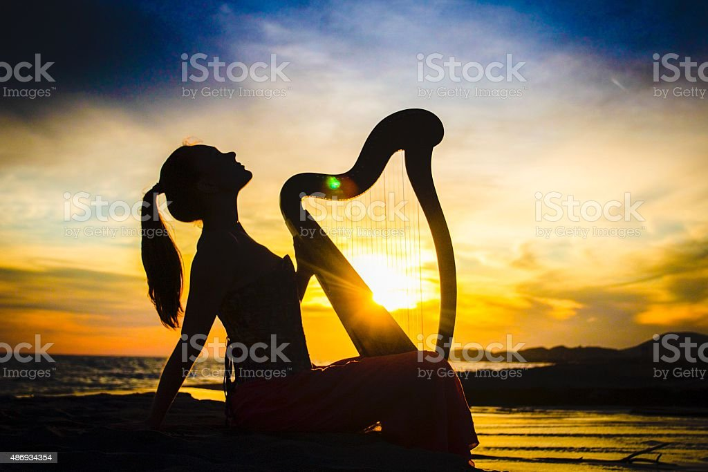 Fairytale harpist silhouette with celtic harp on sunset stock photo