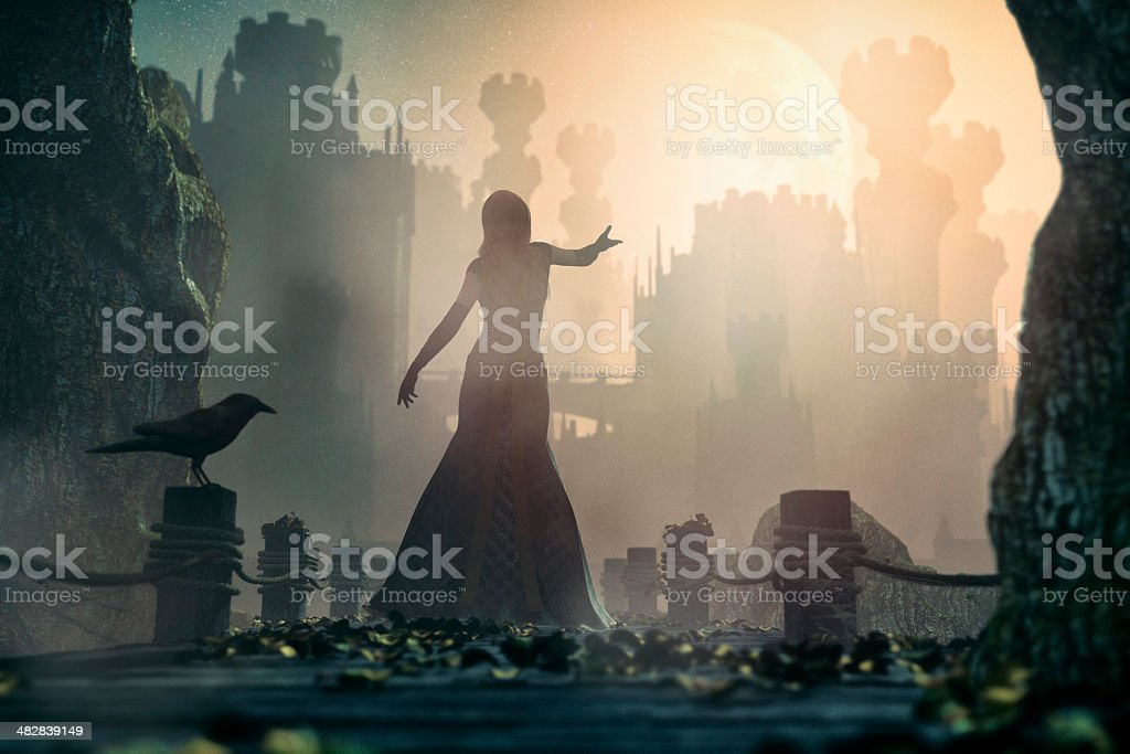 Fairytale princess standing in front of old castle at night stock photo