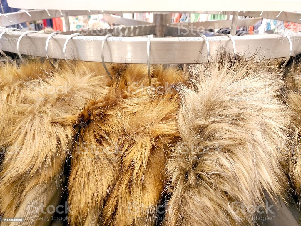 Fake fur coats hanging on clothes rack in store stock photo